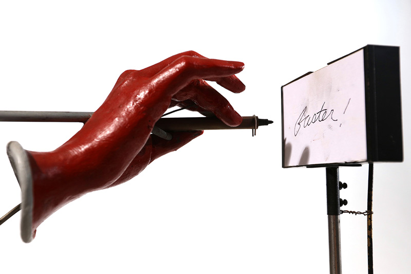 """A mannequin hand writing """"faster"""" on a paper pad."""